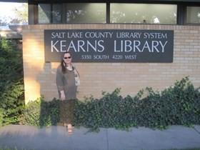 En dame med langt brunt hår og solbriller ikledt grønn genser og langt grønt skjørt står ved et skilt på en vegg i gulbeige mur. Ved bakken vokser det en grønn hekk, og vi ser skyggen av fotografen som tok bildet, til venstre for dama i motivet. Skiltet er avlangt og svart med hvit tekst over tre linjer. På skiltet står det trykt Salt Lake County Library System i middels store bokstaver på øverste linje. På linjen i midten står det Kearns Library i stor skrift. Underst står adressen til biblioteket i middels store bokstaver. Adressen er 5350 South 4220 West