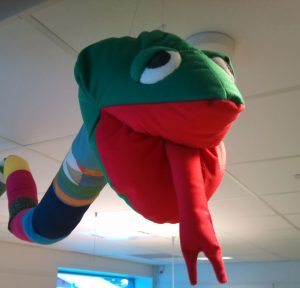 En tøyslange sydd av fargerike stofflapper henger fra et hvitt tak. Tøyslangens grønne hode fyller det meste av bildet, og slangens munn er åpen. Den er sydd i rødt stoff, og en kløyvd rød stofftunge stikker ut ned mot oss. Slangens øyne er halvveis dekt av grønne øyelokk, så han ser litt søvnig ut.
