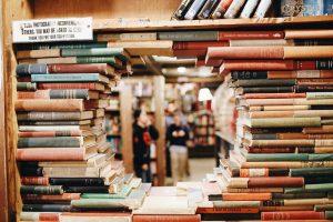 Illustrasjonsbilde av bøker satt opp i sirkel, unge mennesker i bakgrunnen.