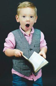 Illustrasjonsbilde av liten gutt som holder ei bok og har et overrasket uttrykk i ansiktet,